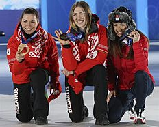 . Sochi (Russian Federation), 15/02/2014.- Gold medalist Darya Domracheva (C) of Belarus is flanked by silver medalist Selina Gasparin (L) of Switzerland...
