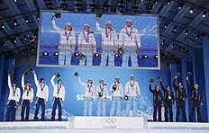 Medallists celebrate celebrate during the award ceremony for the mixed biathlon relay at the Sochi 2014 Winter Olympic Games in Sochi
