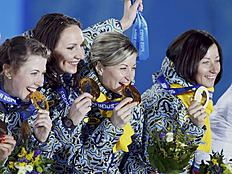 Gold medallists Ukraine's Dzhyma, Vita and Valj Semerenko and Pidhrushna pose during victory ceremony for women's biathlon 4 x 6km event at 2014 Sochi...