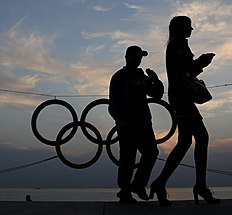Зимние Олимпийские Игры 2014 в Сочи (Winter Olympics 2014): A couple walk past a set of Olympic Rings at a train station overlooking the Black Sea the day after the close of the 2014 Winter Olympics, Monday, Feb...