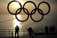 Олимпийские Игры в Сочи-2014 (Winter Olympics Sochi): People watch the sunset while standing under the Olympic rings hanging outside a train station after the 2014 Winter Olympics, Monday, Feb. 24, 2014, in...