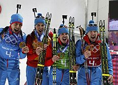 Russia's relay team celebrate during flower ceremony for men's biathlon 4 x 7.5 km relay at Sochi 2014 Winter Olympic Games