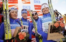 Italy's Katja Haller (L), Lukas Hofer, Christian De Lorenzi and Karin Oberhofer celebrate on the podium after they placed third in the Mixed Relay (2 x 6 + 2 x 7, 5 km) during the biathlon IBU World Cup 2010 in Kontiolahti, Finland, on March 12, 2010.
