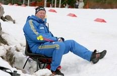 OSLO, NORWAY - MARCH 20: Swedens coach Wolfgang Pichler of Germany sits beside the track and smiles to the camera during the men's pursuit in the E.On Ruhrgas IBU Biathlon World Cup on March 20, 2010 in Oslo, Norway.