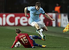 Manchester City's James Milner leaps over a challenge from CSKA's Dmitri Efremov during the Champions League Group E soccer match between CSKA Moscow and...
