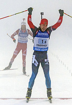 Anton Shipulin of Russia, right, celebrates as he crosses the finish line in front of Ole Einar Bjoerndalen of Norway, left, during foggy weather at the...