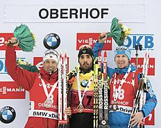 Winner Martin Foucarde of France, center, celebrates besides the 2nd placed Ole Einar Bjoerndalen of Norway, left, and the 3rd placed Timofey Lapshin of...
