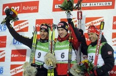 Dominik Landertinger from Austria (C) celebrates his first place on the podium with second Arnd Peiffer of Germany (L) and third Halvard Hanevold of Norway (R) after the men's 15 km mass start event of the Biathlon World Cup in the Siberian city of Khanty-Mansiysk on March 27, 2010.