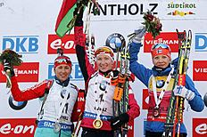 First placed Belarus' Darya Domracheva, center, celebrates on the podium with second placed Russia's Daria Virolaynen, left, and third placed Finland's...