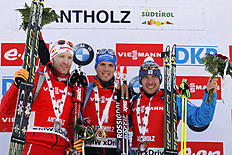 Winner Simon Schempp, center, of Germany, celebrates on the podium with second placed Austria's Simon Eder, left, and third placed Russia's Evgeniy Garanichev...