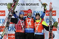 Second placed Simon Schempp from Germany, winner Jakov Fak from Slovenia and third placed Jean-Guillame Beatrix from France, from left to right, celebrate...