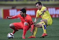 Barcelona's Luis Suarez, from Uruguay, duels for the ball with Villarreal's Cheryshev from Russia during the semifinal, second leg, Copa del Rey soccer...