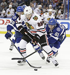 ������ � ������: Chicago Blackhawks right wing Patrick Kane (88), middle, tries to move the puck away from Tampa Bay Lightning right wing Nikita Kucherov (86), left, of...