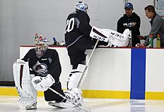 ������ � ������: Colorado Avalanche goalie Semyon Varlamov, front, of Russia, stretches as backup goalie Reto Berra, back, of Switzerland, has the blades cleaned on his...