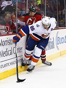 ������ � ������: New York Islanders left winger Nikolay Kulemin (86), of Russia, moves the puck along the boards in front of New Jersey Devils defenseman Vojtech Mozik...