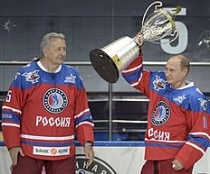 ���������� ������: Putin lifts a trophy as former hockey player Yakushev stands nearby after a gala game, opening a new season of the Night Ice Hockey League in Sochi