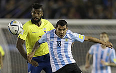 Argentina's Carlos Tevez, right, fights for the ball Ecuador's Gabriel Achilier during a 2018 Russia World Cup qualifying soccer match in Buenos Aires,...