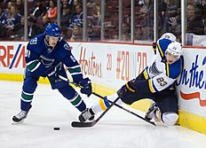 ������ � ������: St. Louis Blues' Dmitrij Jaskin, right, of Russia, passes the puck as he's checked into the boards by Vancouver Canucks' Jared McCann during the first...