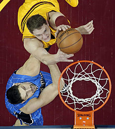 Cleveland Cavaliers' Timofey Mozgov, top, from Russia, drives to the basket against Orlando Magic's Nikola Vucevic, from Montenegro, in the first half of an NBA basketball game Saturday, Jan. 2, 2016, in Cleveland. (AP Photo/Tony Dejak)