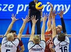 Russia's Sergey Tetyukhin (top, R) spikes the ball during the pool B match Finland vs Russia of the 2016 Men's Volleyball Olympic Qualification tournament in Berlin January 5, 2016. / AFP / John MACDOUGALL