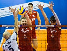 Russia's Sergey Grankin (C) and Artem Volvich (R) try to block a spike by Finland's Antti Siltala during the pool B match Finland vs Russia of the 2016 Men's Volleyball Olympic Qualification tournament in Berlin January 5, 2016. / AFP / John MACDOUGALL