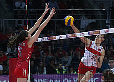 Natalia Malykh (R) of Russia smashes the ball in front of Kubra Akman (L) of Turkey during the CEV volleyball women's 2016 European Olympic Qualification semi final match between Russia and Turkey in Ankara January 8, 2016. / AFP / ADEM ALTAN