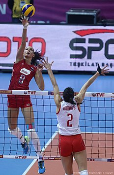 Nataliya Obmochaeva (L) of Russia smashes the ball in front of Gozde K?rdar (R) of Turkey during the CEV volleyball women's 2016 European Olympic Qualification semi final match between Russia and Turkey in Ankara on January 8, 2016. / AFP / ADEM ALTAN