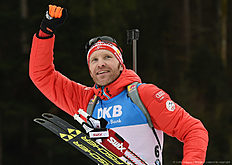 Austrian Simon Eder celebrates during the winner ceremony of the men 12,5 kilometer pursuit competition at the Biathlon World Cup on January 09, 2016 in Ruhpolding, southern Germany. nAustrian Simon Eder won the competition, French Martin Fourcade placed second and Czech Michal Slesingr placed third. / AFP / Christof STACHE