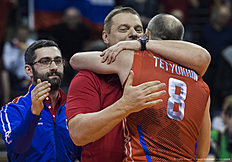Russia's coach Vladimir Alekno (C) embraces Sergey Tetyukhin after Russia defeted Germany 3 to 1 in the semi-final match Germany vs Russia of the 2016 Men's Volleyball Olympic Qualification tournament in Berlin January 9, 2016. / AFP / John MACDOUGALL