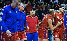 Russia's coach Vladimir Alekno (C) celebrates with his team after Russia defeted Germany 3 to 1 in the semi-final match Germany vs Russia of the 2016 Men's Volleyball Olympic Qualification tournament in Berlin January 9, 2016. / AFP / John MACDOUGALL