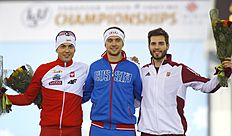 Denis Yuskov, of Russia, centre, who finished in first place, Zbigniew Brodka, of Poland, left, second placed, and Konrad Nagy of Hungary, right, who finished third, pose with their flowers after the men's 500m race at the «Minsk-Arena» Speed Skating Stadium during the European Speed Skating Championship, in Minsk, Belarus, on Saturday, Jan. 9, 2016. (AP Photo/Sergei Grits)