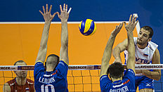 Russia's Alexander Markin spikes the ball in the final match France vs Russia of the 2016 Men's Volleyball Olympic Qualification tournament in Berlin January 10, 2016. / AFP / John MACDOUGALL