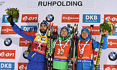 (L-R) Martin Fourcade (2nd) of France, Germany's Erik Lesser (1st) and Evgeniy Garanichev (3rd) of Russia celebrate on the podium after the men's 15 kilometers mass start competition at the Biathlon World Cup on January 16, 2016 in Ruhpolding, southern Germany. / AFP / Christof STACHE