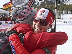 Julia Ranson of Kelowna, British Columbia, is hugged by a friend in the finish area after competing at the biathlon World Cup event in Canmore, Alberta, Canada, Friday, Feb. 5, 2016. (Mike Ridewood/The Canadian Press via AP) MANDATORY CREDIT