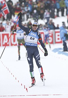 Dominik Windisch of Italy celebrates winning the men's 15-kilometer mass start event at the World Cup biathlon in Canmore, Alberta, Saturday, Feb. 6, 2016. (Mike Ridewood/The Canadian Press via AP) MANDATORY CREDIT