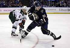 St. Louis Blues' Vladimir Tarasenko, of Russia, keeps his eye on the puck as Minnesota Wild's Christian Folin, left, of Sweden, defends during the second period of an NHL hockey game Saturday, Feb. 6, 2016, in St. Louis. (AP Photo/Jeff Roberson)