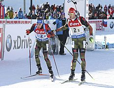 Arnd Peiffer, right, of Germany, hands off to teammate Simon Schempp in the team mixed relay at the IBU biathlon World Cup in Canmore, Alberta, Sunday, Feb. 7, 2016. (Mike Ridewood/The Canadian Press via AP) MANDATORY CREDIT