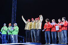 (L-R) Germany's, Norway's and Canada's teams celebrate during the medals ceremony after the Men 4 x 7,5 km Relay event at the IBU World Championships Biathlon competition in Oslo Holmenkollen, on March 12, 2016.nNorway won the event ahead of Germany (2nd) and Canada (3rd). / AFP / JONATHAN NACKSTRAND