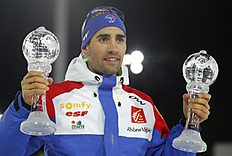 Martin Fourcade of France celebrates with his Men's Overall World Cup Sprint and Individual trophies during the award ceremony at the IBU Biathlon World Cup finals, in Khanty-Mansiysk, 2759 km north-east of Moscow, Russia, Friday March 18, 2016. (AP Photo/Sergei Grits)