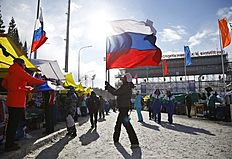 A man holds Russian flag at the sport complex of the IBU World Championships Biathlon at Khanty-Mansiysk, 2759 km north-east of Moscow, Russia, Sunday, March 20, 2016. All races were cancelled due to the weather conditions. (AP Photo/Sergei Grits)
