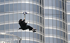 In this April 9, 2016 photo, a woman enjoys an urban zip line attraction in Dubai, United Arab Emirates. In the air travel hub of Dubai, there's a new way to fly: A zip line run by extreme sports company XDubai. XDubai, which began its operations in 2015, and is associated with Sheikh Hamdan bin Mohammed bin Rashid Al Maktoum, the crown prince of Dubai. (AP Photo/Kamran Jebreili)