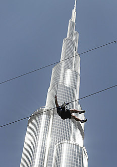 In this April 9, 2016 photo, with the world's tallest tower, Burj Khalifa, in background, a man enjoys an urban zip line attraction in Dubai, United Arab Emirates. In the air travel hub of Dubai, there's a new way to fly: A zip line run by extreme sports company XDubai. XDubai, which began its operations in 2015, and is associated with Sheikh Hamdan bin Mohammed bin Rashid Al Maktoum, the crown prince of Dubai. (AP Photo/Kamran Jebreili)