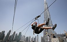In this April 9, 2016 photo, with the world's tallest tower, Burj Khalifa, in backdrop, a man enjoys an urban zip line attraction in Dubai, United Arab Emirates, Saturday, April 9, 2016. In the air travel hub of Dubai, there's a new way to fly: A zip line run by extreme sports company XDubai. XDubai, which began its operations in 2015, and is associated with Sheikh Hamdan bin Mohammed bin Rashid Al Maktoum, the crown prince of Dubai. (AP Photo/Kamran Jebreili)