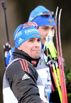 German Michael Greis (L) grimaces on the podium of the men's 10 km sprint event of the Biathlon World Cup in Anterselva on January 20, 2011. Russian Anton Shipulin (back) won ahead of German Michael Greis and Norwegian Lars Berger.