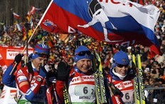 Team Russia's Svetlana Sleptsova (R), Anna Bogaliy-Titovets (C) and Olga Zaitseva pose as their teammate Natalia Guseva waves a national flag behind them at the finish area at the end of the women's 4x6km relay at the Biathlon World Cup at a ski resort in Anterselva, northeast of Italy January 22, 2011. Russia won the competition ahead of second-placed Sweden and third-placed Germany.