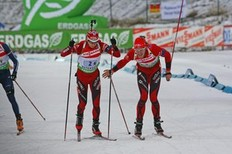 OSTERSUND, SWEDEN - DECEMBER 06: Ole Einar Bjoerndalen (L) of Norway takes over from Lars Berger of Norway during the Men's 4x7.5 km Relay in the E.ON Ruhrgas IBU Biathlon World Cup on December 6, 2009 in Ostersund, Sweden.