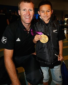AUCKLAND, NEW ZEALAND — AUGUST 15: Rower Mahe Drysdale of the New Zealand Olympic team poses with Nico Mu and his gold medal at Auckland International Airport after competing in the 2012 London Olympic Games on August 15, 2012 in Auckland, New Zealand.