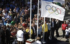 Rio de Janeiro's Governor Sergio Cabral hangs a replica of the Olympic flag as the original is seen inside a box (bottom L) at Complexo do Alemao slum during a ceremony to mark its arrival in Rio de Janeiro, after the London 2012 Olympic Games, August 15, 2012. Brazil will host the 2016 Olympic Games.