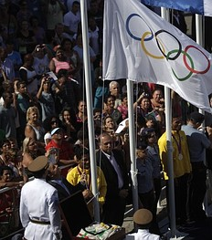 Rio de Janeiro's Governor Sergio Cabral raises a replica of the Olympic flag as the original is seen inside a box (bottom L) at Complexo do Alemao slum during a ceremony to mark its arrival in Rio de Janeiro, after the London 2012 Olympic Games, August 15, 2012. Brazil will host the 2016 Olympic Games.