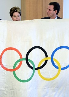 Rio de Janeiro Mayor Eduardo Paes (R) and Brazil's President Dilma Rousseff pose behind the Olympic flag in Brasilia August 14, 2012. Brazil will host the 2016 summer games.